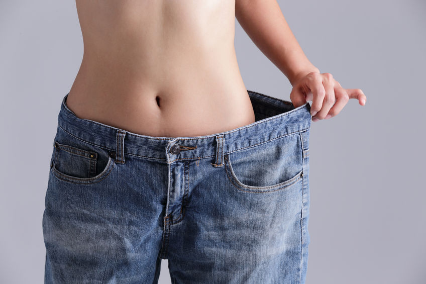 woman shows weight loss by wearing old jeans - (Weight Loss Surgery)